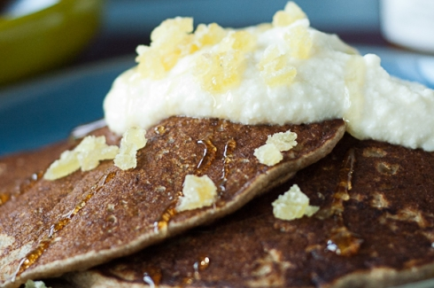 close-up buckwheat pancakes with ricotta, honey, and ginger topping